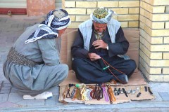 Crafty gentlemen: A Kurdish man strings beads as he chats with a friend in the central square of Erbil, Iraq. (2010)
