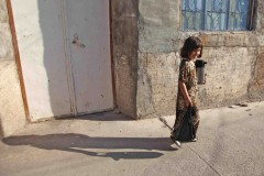 Coffee run: A young Kurdish girl totes a coffee urn through the side streets in Erbil, Iraq. (2010)