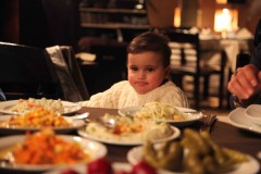 Inedible options: Omar Omar stares down an impressive array of dishes, few of which he can chew, and none of which he can reach. (2010)