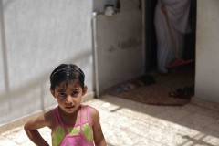 Seeking shade: A little girl stands in the front room of her family's home in the Al-Shati, or Beach Refugee Camp in the northern Gaza strip. (2010)