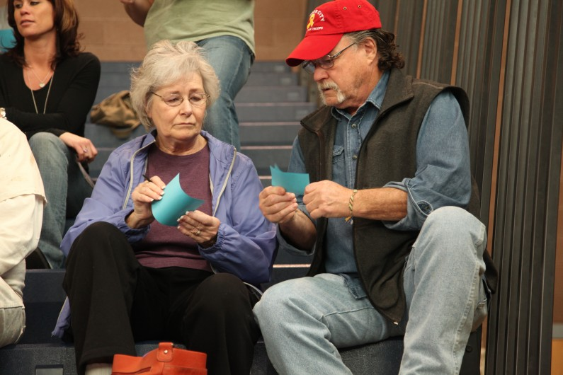 GOP caucus-goers compare notes before casting ballots at Boulder City High School in Boulder City, N.V. (2012)