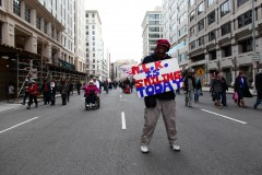 Roderick Beechum of Virgina displays a sign while walking down H Street NW in Washington, D.C., a few blocks away from the National Mall on Inauguration Day. (2013)